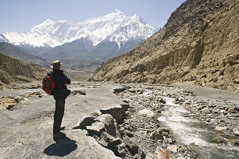 Trekker enjoys the view on the Annapurna circuit trek, Jomsom, Himalayas, Nepal. The high peak in the distance is 7021m Nilgiri, forming part of a wall known as The Grand Barrier. Model released.