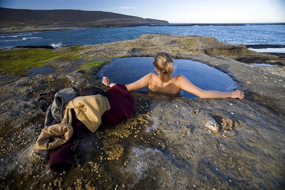 Woman relaxing in natural pool by the Atlantic Ocean, Santa Cruz, Argentina, South America
