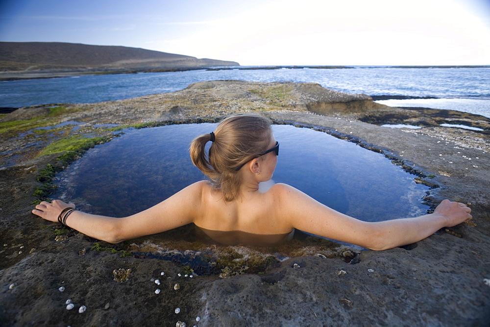 Young woman relaxing in a natural pool, Santa Cruz, Argentina, South America