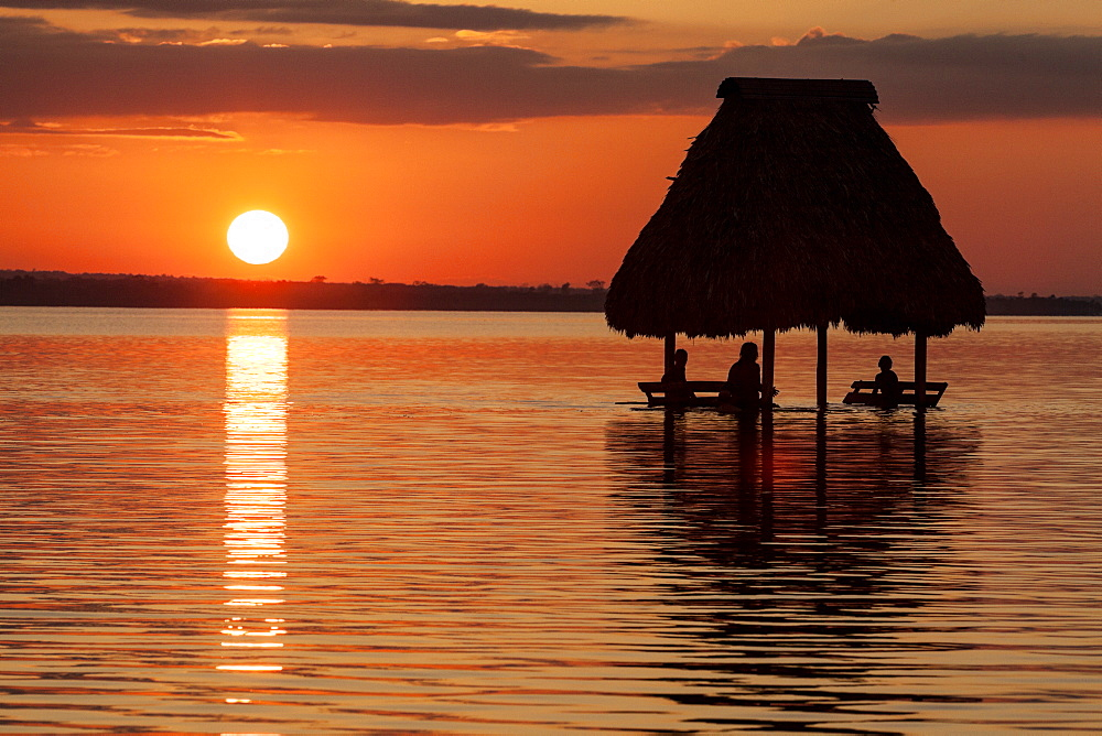 People relaxing at sunset, Lago Peten Itza, El Remate, Guatemala, Central America