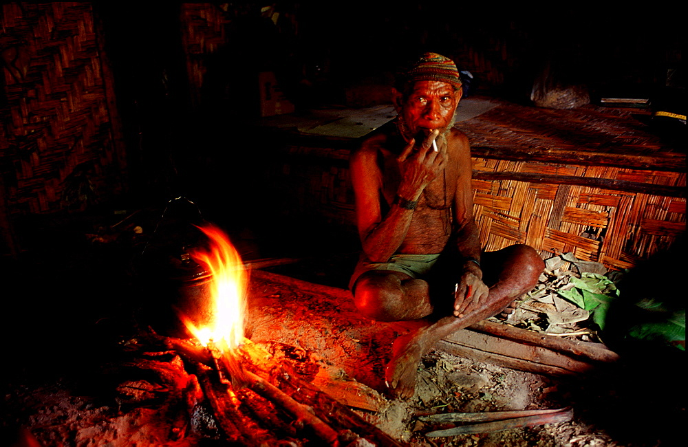 Huli makes fire in his house, Papua New Guinea, Tari, Huli, Highlands