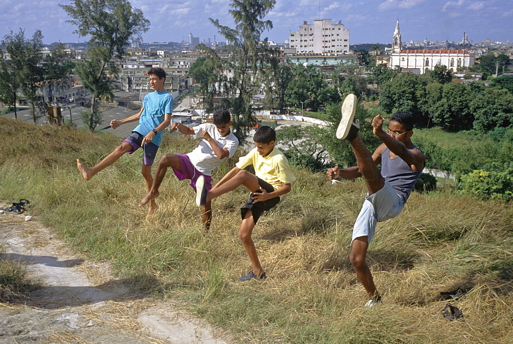 Four boys practicing kick boxing, martial arts moves in the El Cerro area of Havana, Cuba