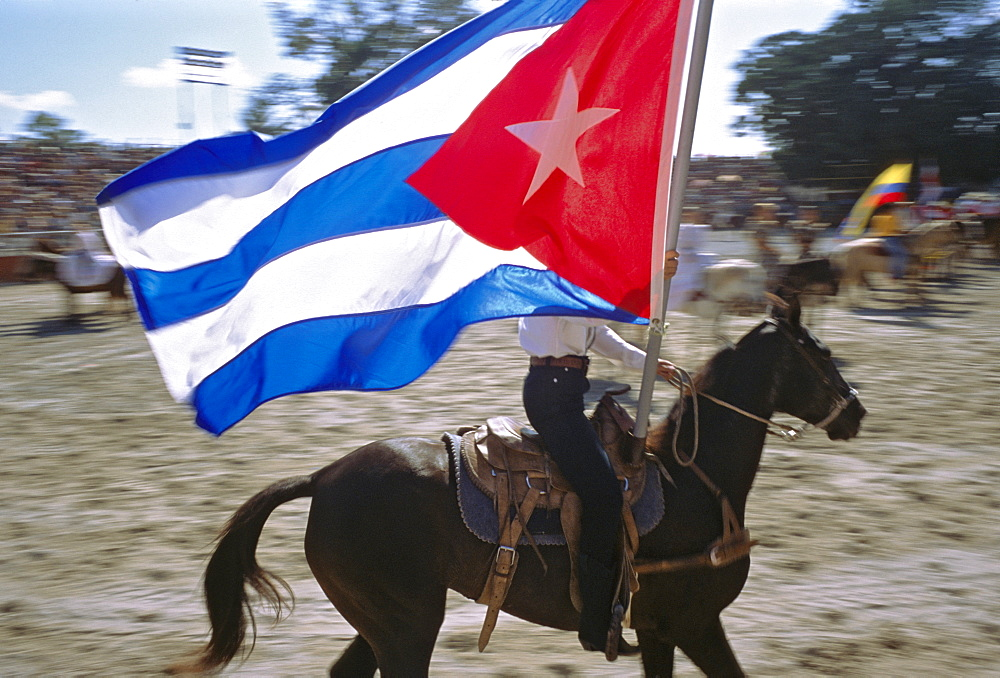 A horseback rider carries the Cuban flag in the opening ceremony of a rodeo in Havana, Cuba