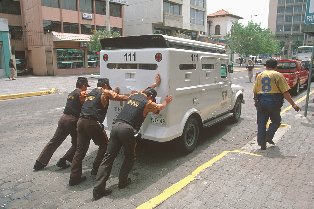 Ecuador's capital and second largest city guards pushing stalled armour car on Av Amazonas in New Town banking area, Quito, Ecuador