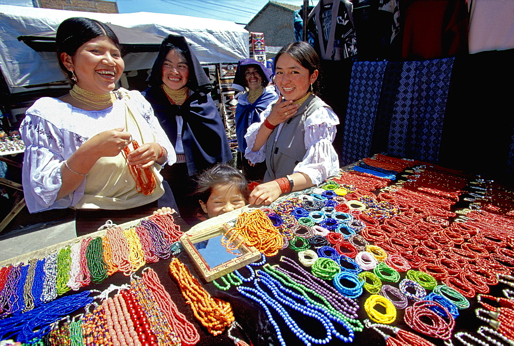 Otavalo, north of Quito is one of Latin Am's most famous markets for textiles, crafts and produce Otavalo women buying necklaces, Quito, Ecuador