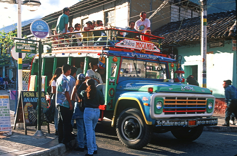 Banos resort and famous hot springs and site of Basilica of Senora de Agua Santa teens on street boarding a local bus, Highlands, Ecuador