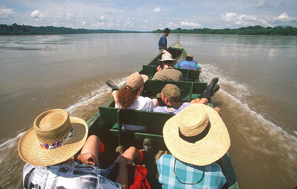 Amazon Basin, Napo River (tributary) La Selva Jungle Lodge, naturalists in dugout canoe on the Napo passing through rainforest, Amazon, Ecuador - 763-448