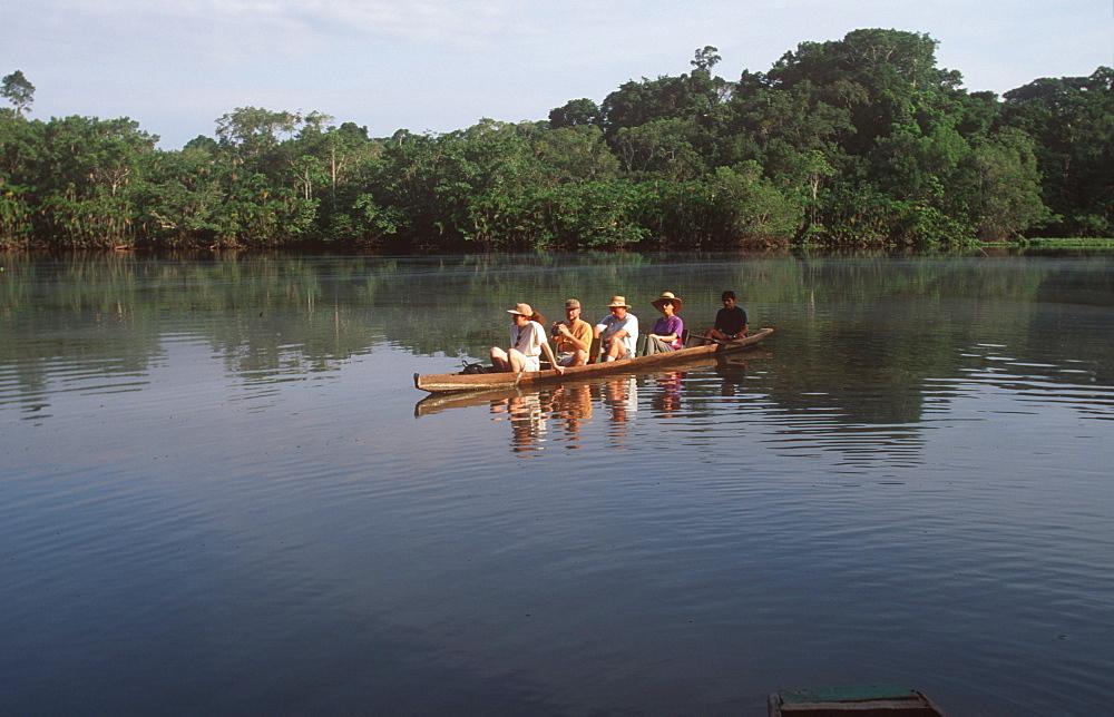 Amazon Basin, Napo River (tributary) La Selva Jungle Lodge, naturalists in dugout canoe on jungle stream in primary rainforest, Amazon, Ecuador