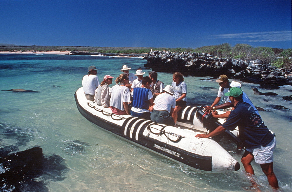 Hood Island tourists in inflatable raft with naturalist during an ecotourism trip, Galapagos Islands, Ecuador