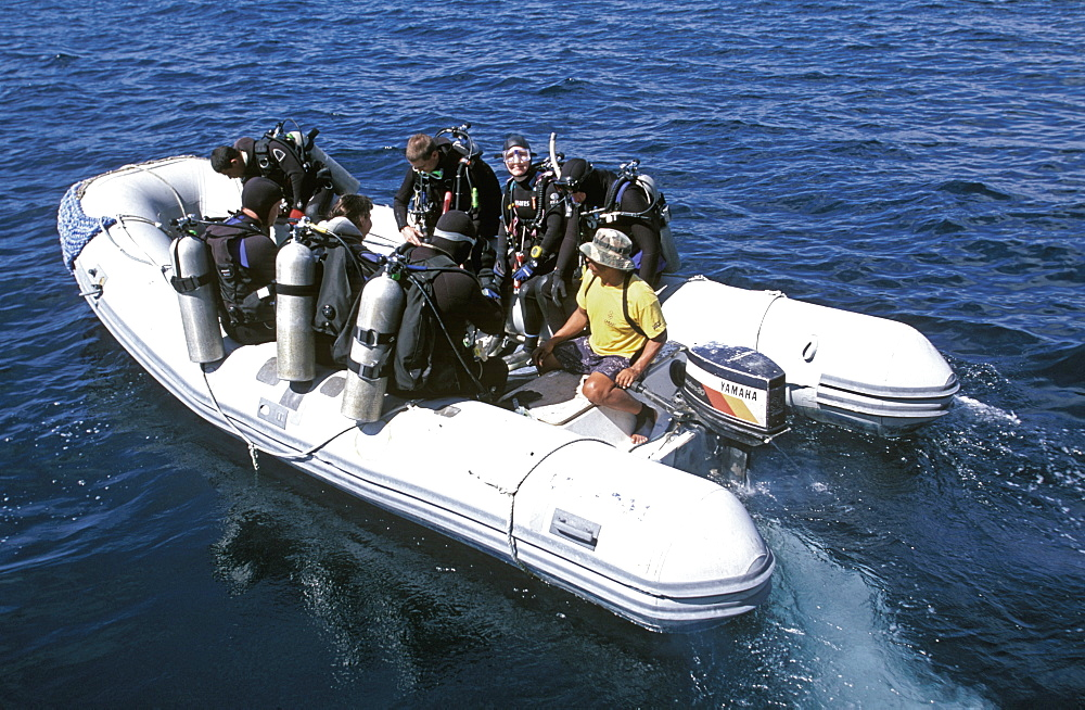 Scuba divers in an inflatable tender taking them to their dive site off Wolf Island, one of the most northerly of the islands, Galapagos Islands, Ecuador