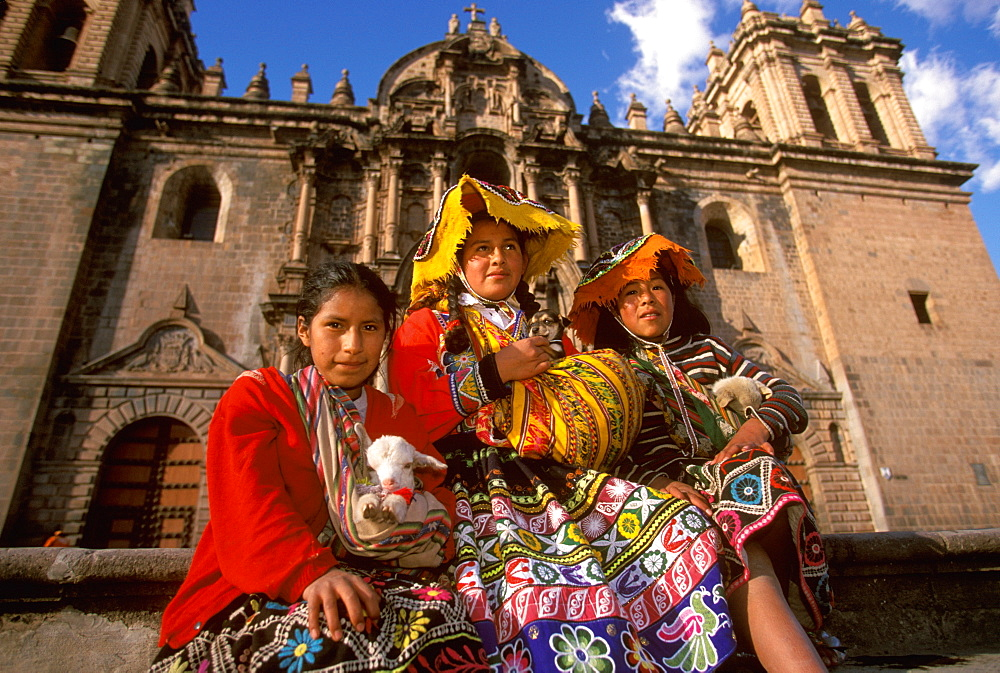 Ancient capital of the Incas the Plaza de Armas with young girls in traditional dress on the steps in front of the Cathedral, Cuzco, Highlands, Peru