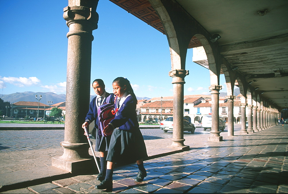 The Plaza de Armas, in the old colonial city with two young school girls walking under arcade, Cuzco, Highlands, Peru