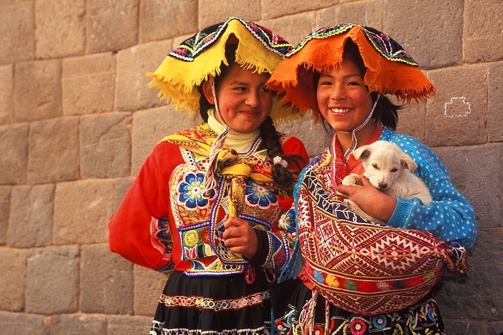 Two young Indian girls in traditional dress in front of a finely cut Inca Wall on Calle Loretto in the heart of the colonial center, Cuzco, Highlands, Peru
