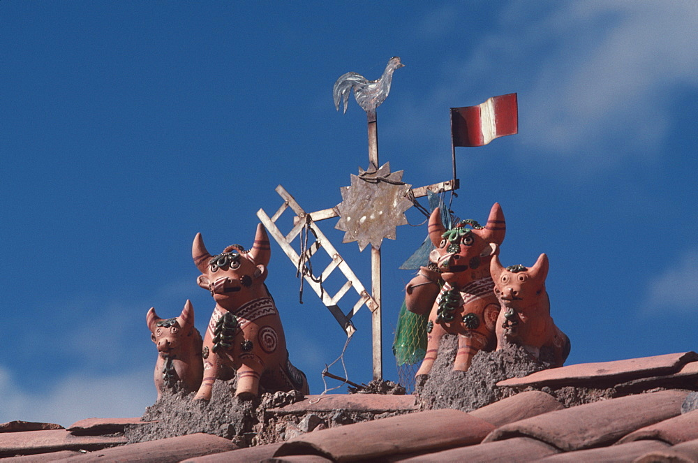Folk art particular to the Cuzco area are the small bulls or 'toritos' placed on roofs of new homes to bring good luck to inhabitants, Cuzco, Highlands, Peru
