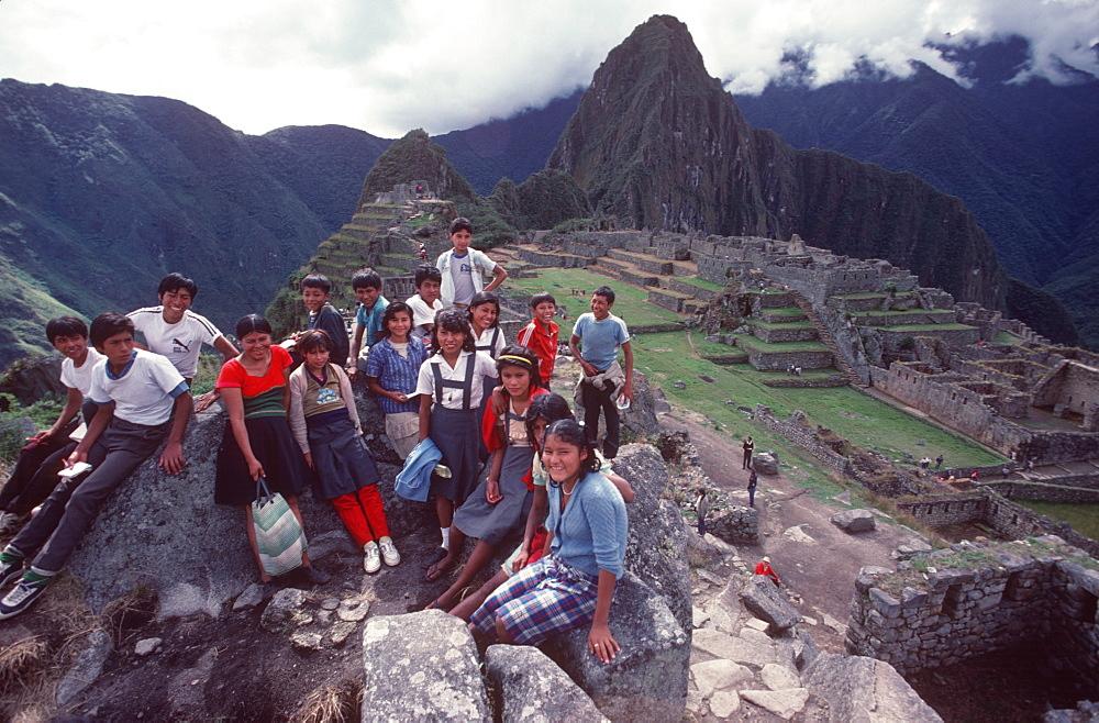 Machu Picchu view of the ancient city with Huayna Picchu Peak above the Rio Urubamba Peruvian school children visiting the site, Highlands, Peru