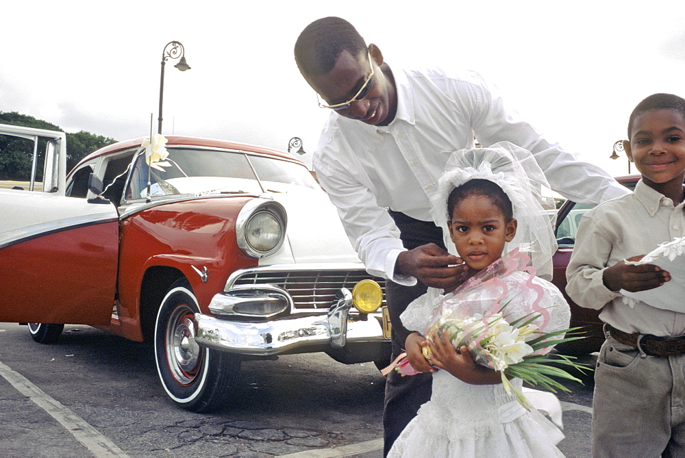 Flower girl with her father coming from the wedding ceremony in their vintage American car, Cuba
