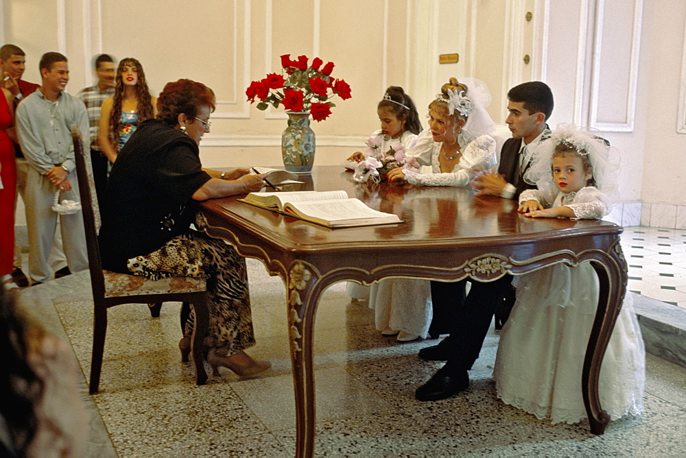 A bride and groom and their wedding party at their civil wedding ceremony in the Palacio de los Matrimonios in Centro Habana, Havana, Cuba