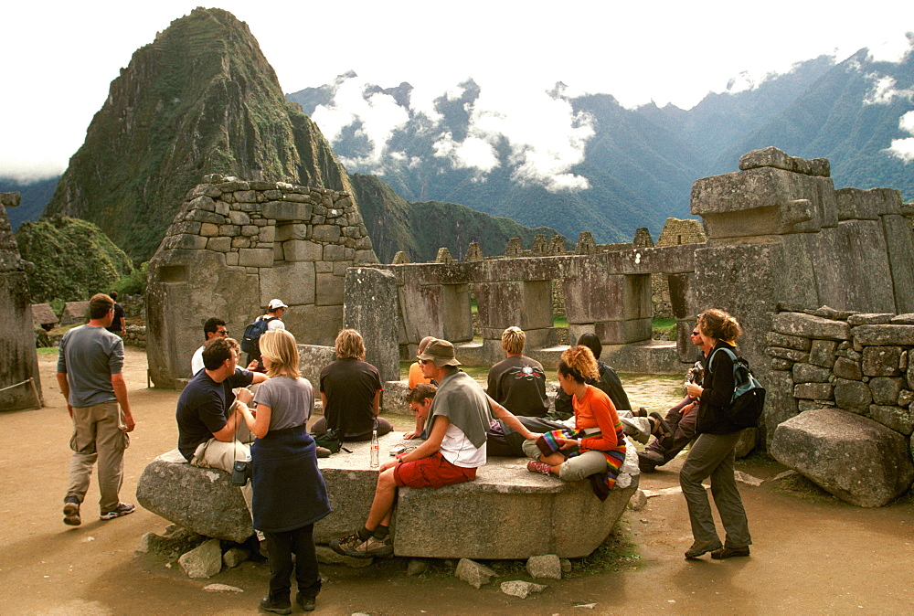 Machu Picchu the ancient city with visitors viewing the temples in the Sacred Precinct, Highlands, Peru - 763-882