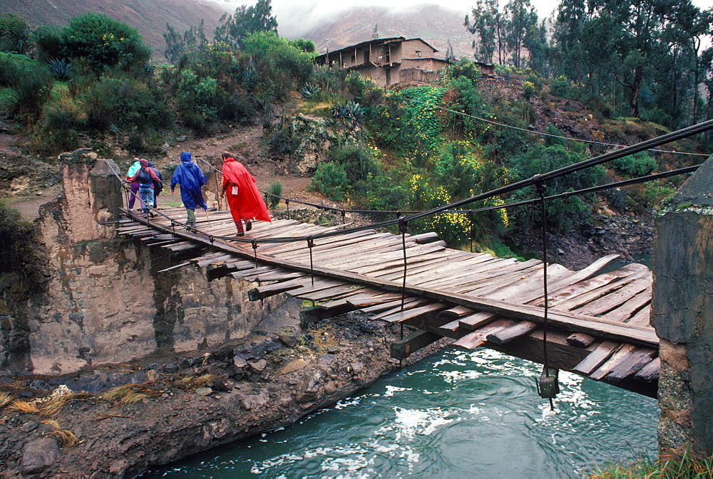 Hikers on the Inca Trail passing over the Urubamba River on a suspension bridge near Chilca on the way to Machu Picchu, Peru