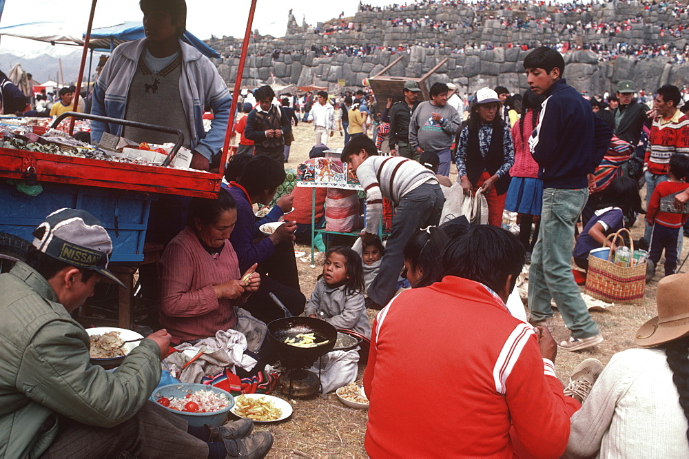 Inti Raymi spectators eating lunch during the Incan Festival of the Sun, held at Sacsayhuaman, above Cuzco on June 24th, Peru