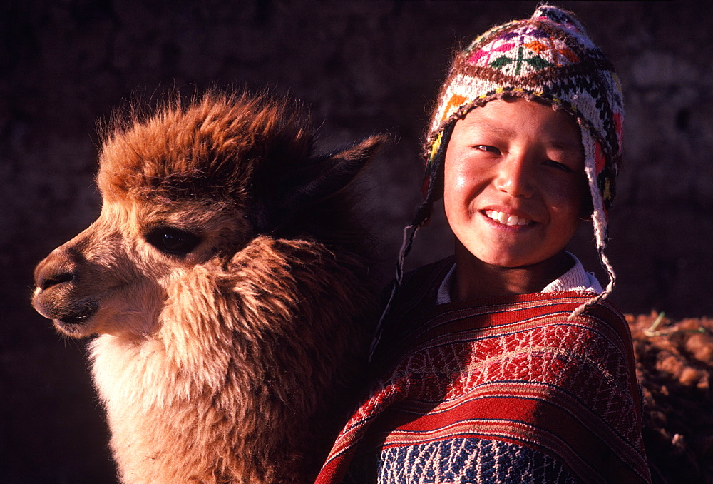 A young Quechua boy dressed in traditional hat and serape with his pet a young alpaca near Cuzco, Peru