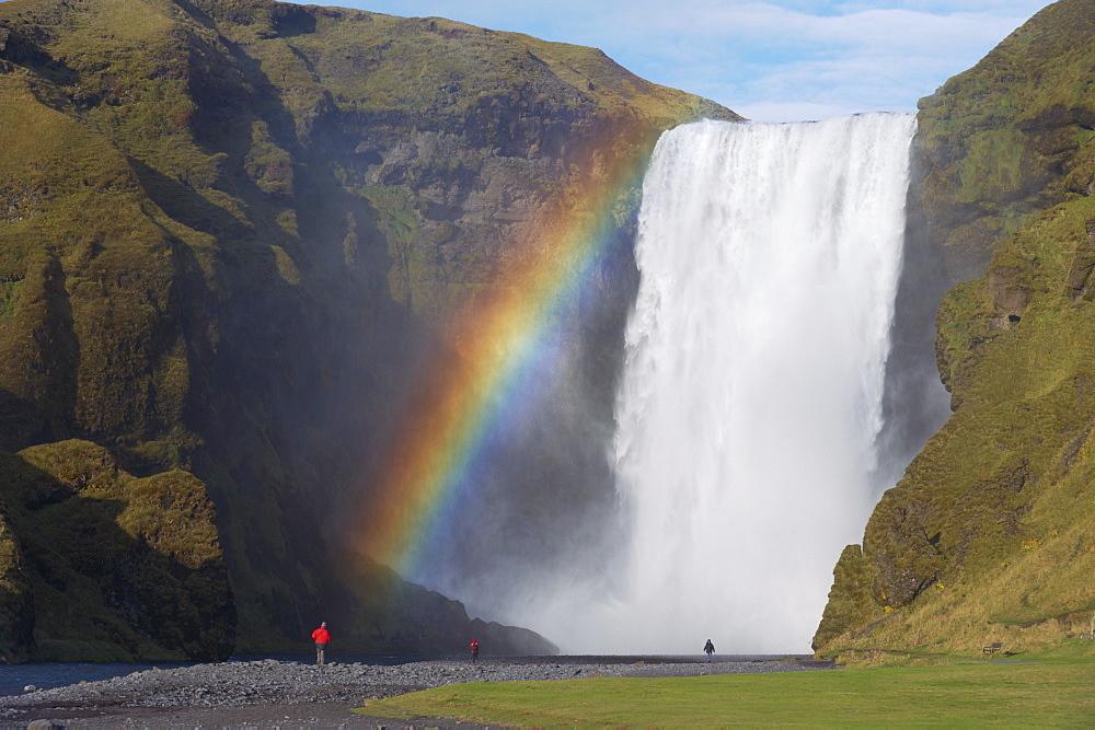 Tourist in red jacket at 62 m high Skogafoss waterfall, Skogar, South area, Iceland, Polar Regions