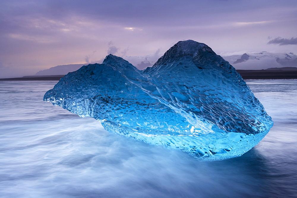 Translucent blue iceberg washed ashore on Breidamerkursandur black sands, near Jokulsarlon glacial lagoon, Oraefajokull (Vatnajokull) glacier in the distance, East Iceland, Polar Regions