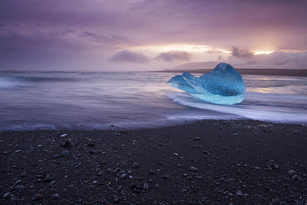 Translucent blue iceberg washed ashore on Breidamerkursandur black sands, near Jokulsarlon glacial lagoon, East Iceland, Iceland, Polar Regions