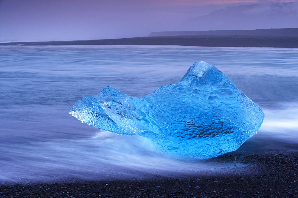 Translucent blue iceberg washed ashore on Breidamerkursandur black sands, near Jokulsarlon glacial lagoon, East Iceland, Polar Regions