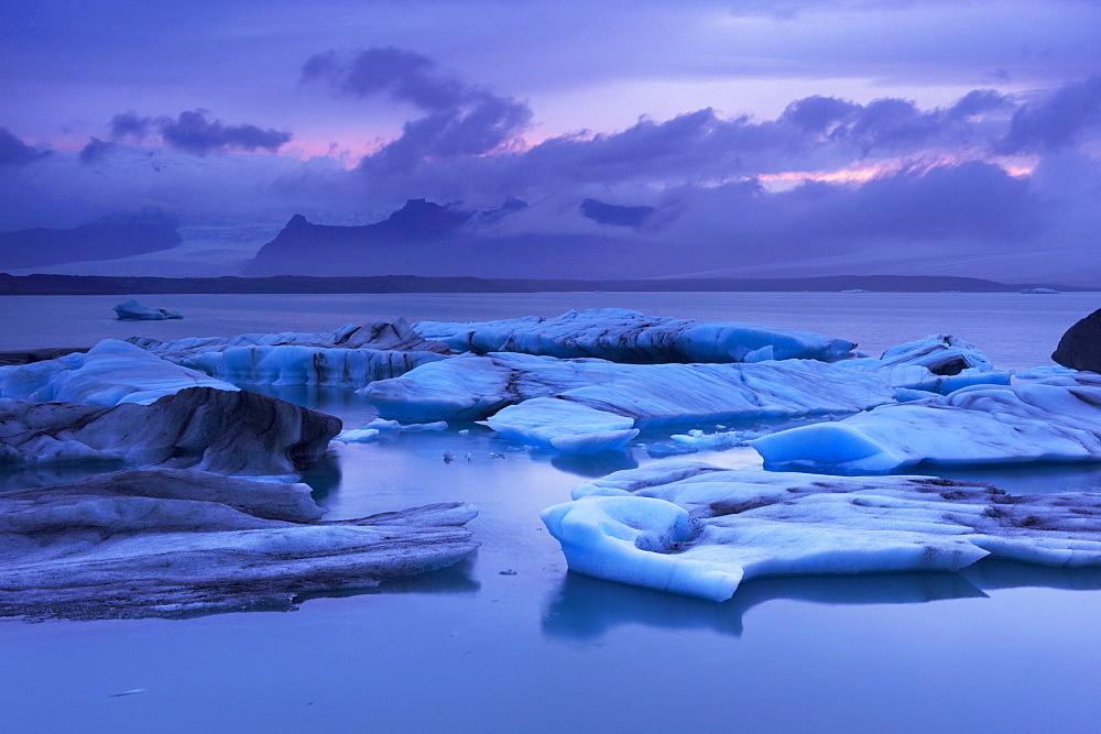 Icebergs in Jokulsarlon glacial lagoon, at dusk, Oraefajokull (Vatnajokull) glacier in the distance, East Iceland, Iceland, Polar Regions - 770-1354