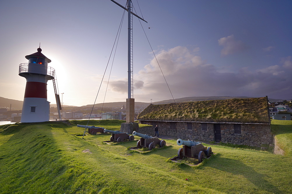 Skansin fort, old fort guarding Torshavn and its harbour (old brass cannons, WW2 british marine guns and lighthouse), Nolsoy in the distance, Torshavn, Streymoy, Faroe islands (Faroes), Denmark, Europe.