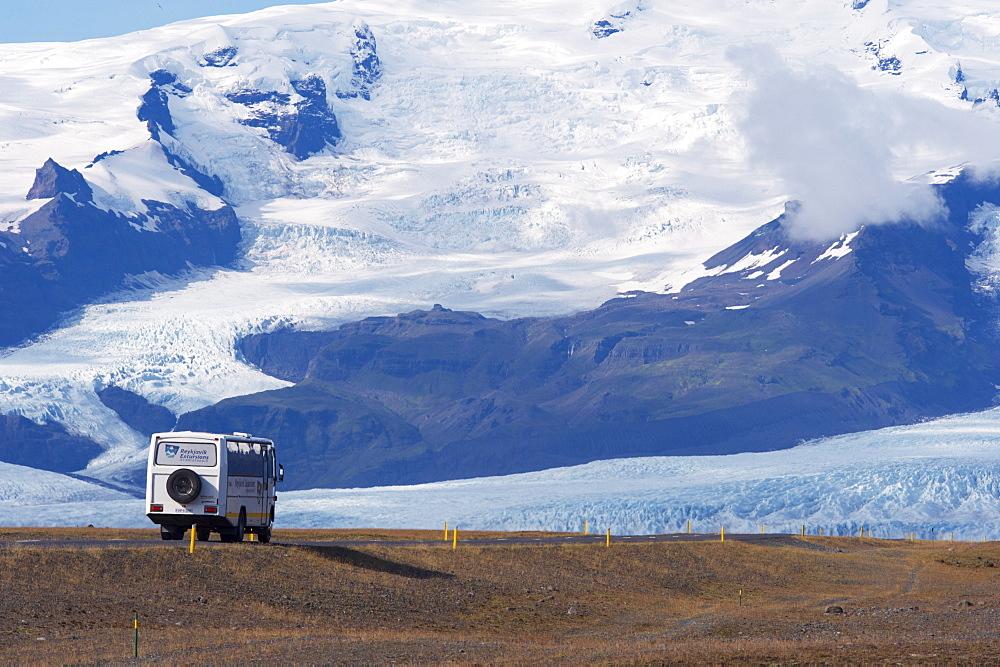 A tourist bus on the ring road (Route 1) beneath the huge mass of Oraefajokull (Vatnajokull) glacier, south-west Iceland (Austurland), Iceland, Polar Regions