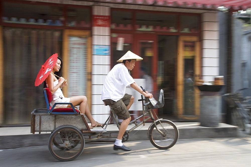 Asian woman (Chinese-Thai) riding in cycle rickshaw, Hutong District, Beijing, China, Asia
