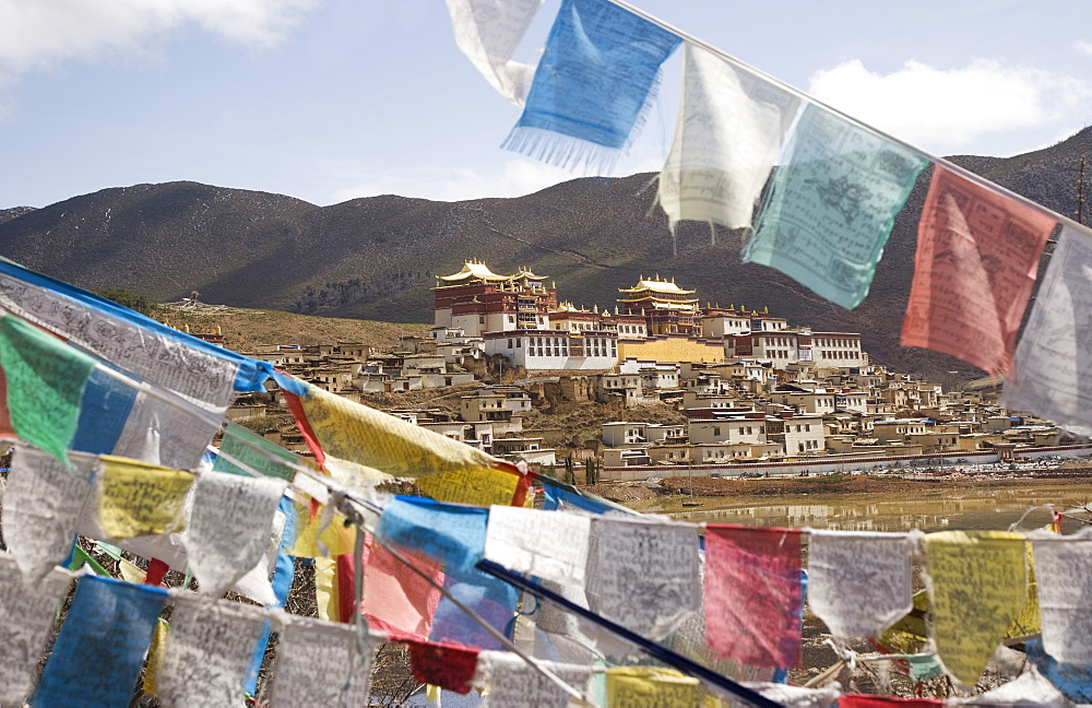 Prayer flags and Ganden Sumsteling Gompa (Gandan Sumtseling) (Songzanlin Si) Buddhist Monastery, Shangri-La, formerly Zhongdian, Shangri-La region, Yunnan Province, China, Asia