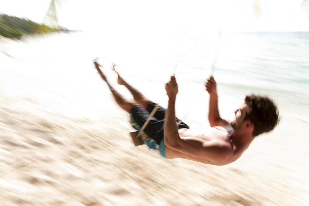 Man swinging on the beach, Kuramathi Island, Ari Atoll, Maldives, Indian Ocean, Asia