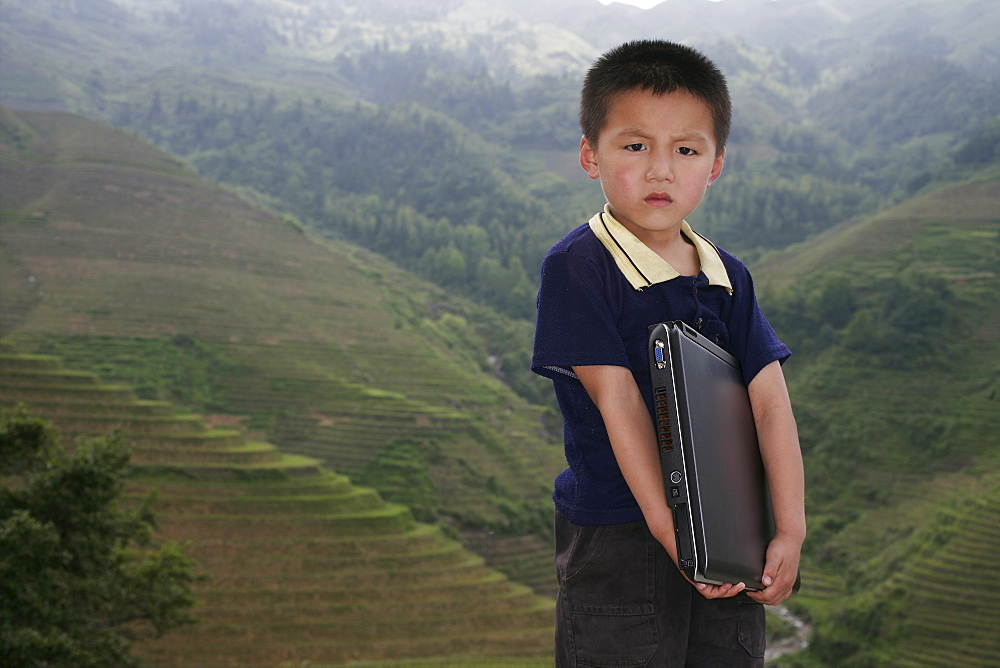 Boy of Yao mountain tribe minority with laptop, Longsheng terraced ricefields, Guangxi Province, China, Asia