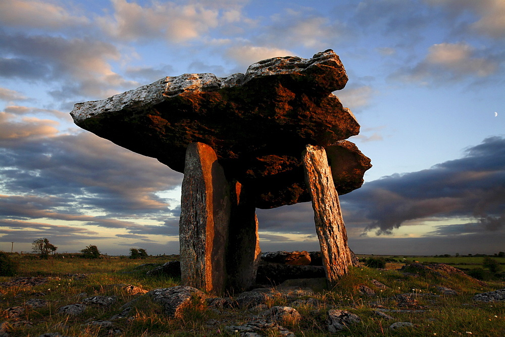 "Poulnabrone dolmen megalithic tomb, Burren, County Clare, Munster, Republic of Ireland (Eire), Europe *** Local Caption *** The Burren (from Irish: Boireann, meaning - great rock) is a unique karst landscape in northwest County Clare, Ireland. The limestone area measures 300 square kilometres and is roughly enclosed within the circle comprised by the villages Ballyvaughan, Kinvarra, Gort, Corrofin, Kilfenora, Lisdoonvarna and the Black Head lighthouse. The definitive article (ie ""The"" Burren) has only been added to the name by academics in the last few decades as it has always been traditionally called Boireann or Boirinn in Irish and Burren in English."