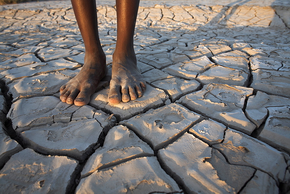 A boy stands in the desolate landscape of Lac Abbe, Djibouti, Africa