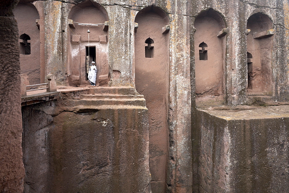A priest stands at the entrance to the rock-hewn church of Bet Gabriel-Rufael, in Lalibela, UNESCO World Heritage Site, Ethiopia, Africa