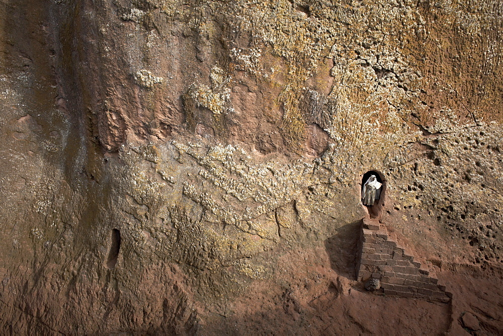 A woman emerges from a tunnel leading to the rock-hewn church of Bet Amanuel, in Lalibela, Ethiopia, Africa