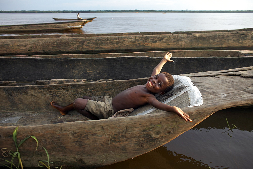 A boy relaxes in a dugout canoe on the Congo River, Yangambi, Democratic Republic of Congo, Africa