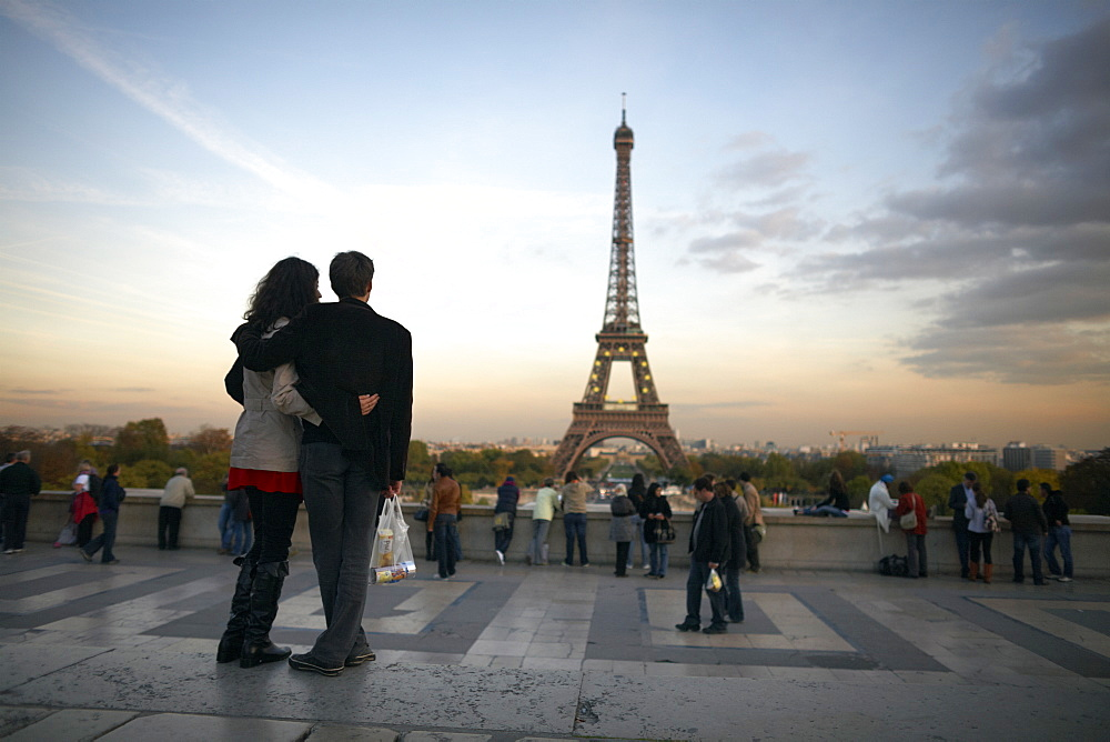 A couple look towards the Eiffel Tower, Paris, France, Europe