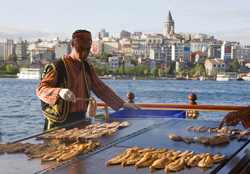 Man cooking fish on a  boat on the Golden Horn with the Galata Tower and Beyoglu district in the background, Istanbul, Turkey, Europe