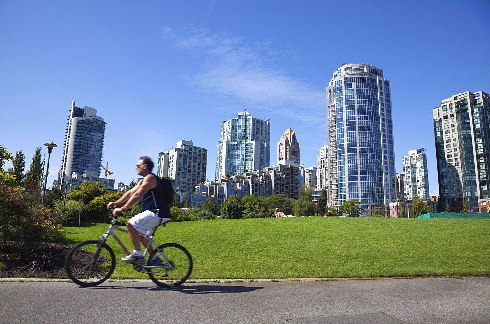 Cyclist passing apartment blocks, False Creek, Vancouver, British Columbia, Canada, North America