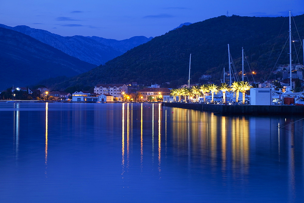 Waterfront at dusk at the newly developed Marina in Porto Montenegro with mountains behind, Montenegro, Europe