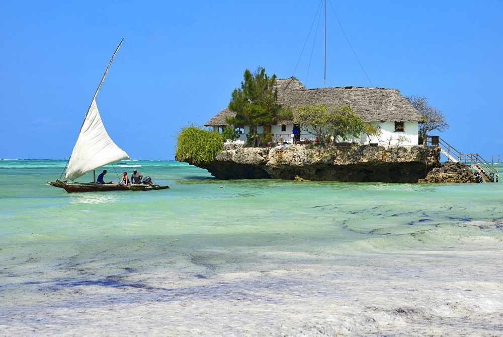 Tourist on a traditional Dhow boat, The Rock Restaurant, Bwejuu Beach, Zanzibar, Tanzania, Indian Ocean, East Africa, Africa