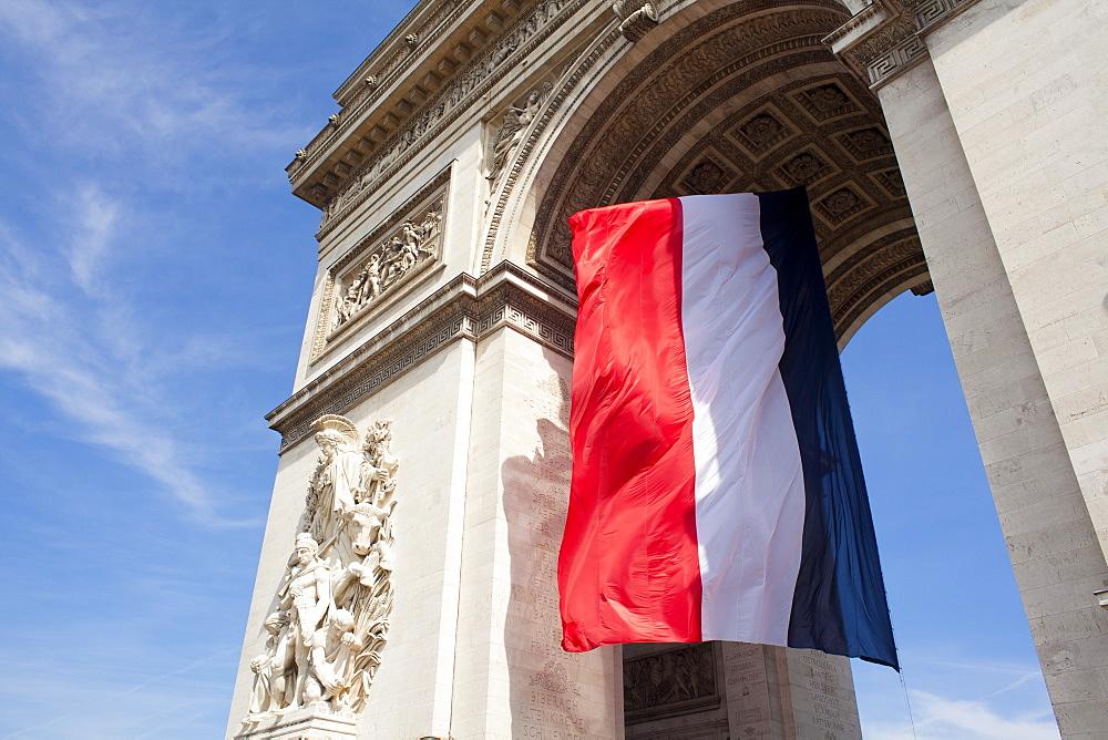 French flag under Arc de Triomphe built by Napoleon, Paris, France, Europe