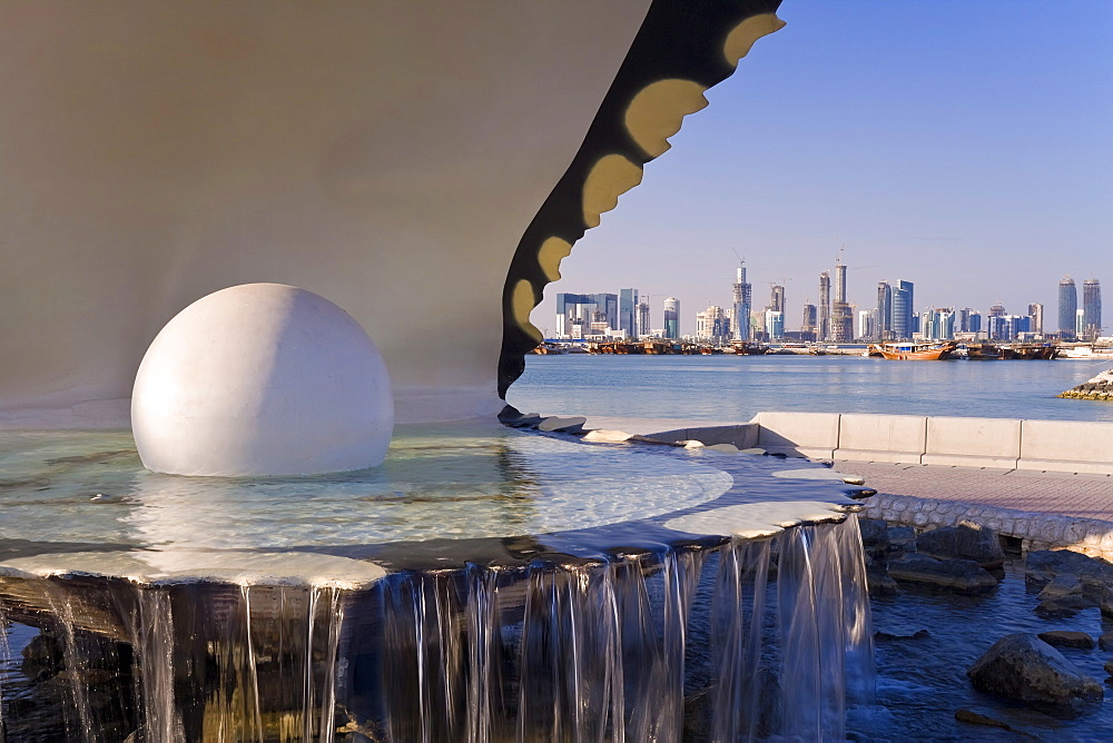Pearl Monument on the Corniche of Doha Bay with the centra business district of the West Bay on the horizon, Doha, Qatar, Middle East