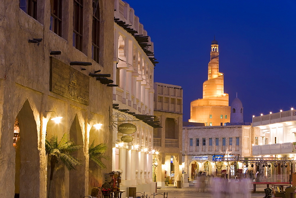 The restored Souq Waqif looking towards the illuminated spiral mosque of the Kassem Darwish Fakhroo Islamic Centre based on the Great Mosque of Samarra in Iraq, Doha, Qatar, Middle East
