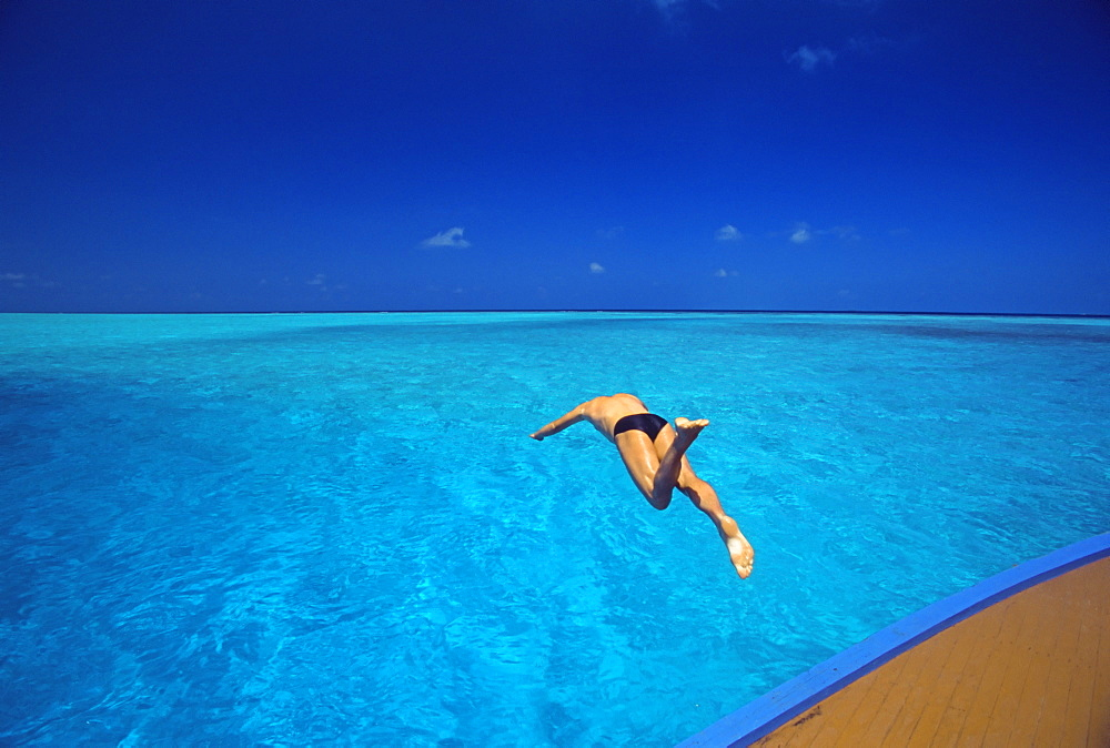 Man jumping into tropical sea from deck, Maldives, Indian Ocean, Asia - 795-104